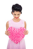 Pleased black hair model holding a pink heart shaped pillow