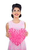 Content black hair model holding a pink heart shaped pillow