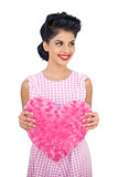 Cheerful black hair model holding a pink heart shaped pillow