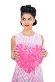 Pretty black hair model holding a pink heart shaped pillow
