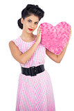 Cute black hair model holding a pink heart shaped pillow