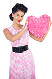 Playful black hair model holding a pink heart shaped pillow