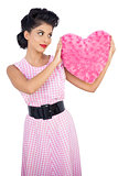 Stylish black hair model holding a pink heart shaped pillow