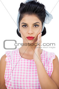 Serious black hair model posing with a hand on the cheek