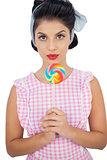 Serious black hair model holding a colored lollipop