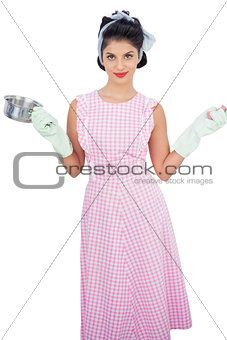 Smiling black hair model holding a pan and wearing rubber gloves