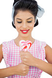 Content black hair model holding a heart shaped lollipop