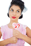 Pensive black hair model holding a heart shaped lollipop
