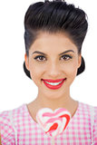 Happy black hair model holding a heart shaped lollipop