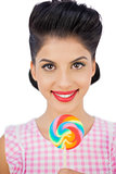 Joyful black hair model holding a colored lollipop
