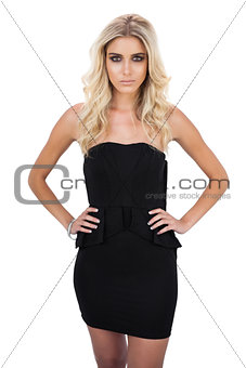 Unsmiling blonde model in black dress posing hands on the hips