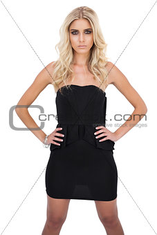Serious blonde model in black dress posing hands on the hips