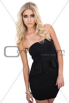 Serious blonde model in black dress posing looking at camera