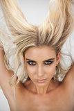 Charming blonde model in black dress posing holding her hair
