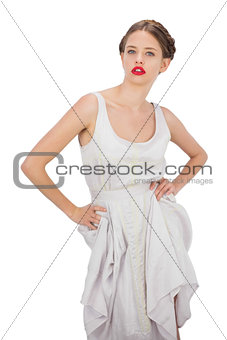 Severe model in white dress posing hands on the hips