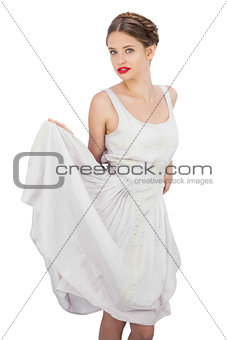 Gorgeous model in white dress posing holding her dress