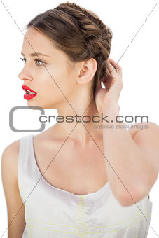 Puzzled model in white dress touching her hair and looking away