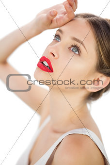 Elegant model in white dress posing with a hand on her forehead