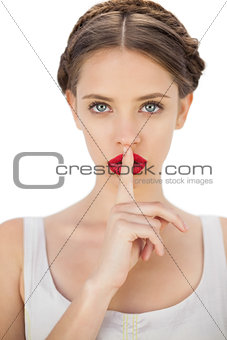 Mysterious model in white dress posing with a finger on her mouth