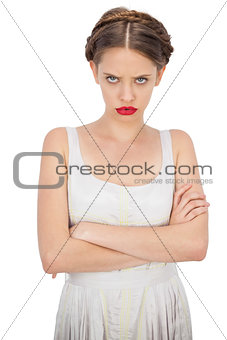 Frowning model in white dress posing with crossed arms