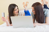 Pretty friends using a laptop to shop online lying on bed