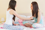 Girls in pajamas talking on bed