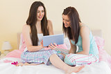 Girls in pajamas talking on bed using a tablet