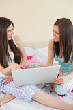Smiling friends in pajamas talking on bed using a laptop
