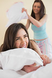 Cheerful friends in pajamas having a pillow fight on bed