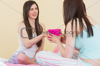 Smiling girl in pajamas giving a present to her friend