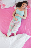 Brunette in pajamas lying on bed and smiling at camera