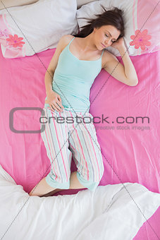 Brunette in pajamas sleeping on bed