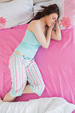 Pretty brunette in pajamas sleeping on bed