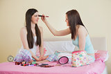 Smiling girl giving her friend a makeover at sleepover