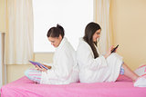 Two friends wearing bathrobes sitting back to back using smartphone and tablet