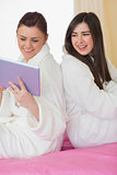 Two smiling friends wearing bathrobes sitting back to back looking at tablet