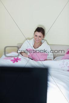 Laughing teen wearing bathrobe watching tv