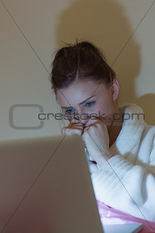 Pretty teen wearing dressing gown watching her laptop in the dark