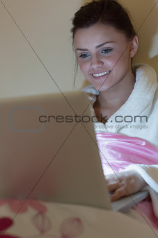 Pretty teen wearing dressing gown using her laptop in the dark
