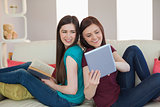 Girl showing her friend her tablet pc on the sofa
