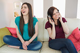 Girl listening to music with her friend beside her on the sofa
