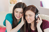 Cheerful girl listening to music with her friend beside her on the sofa