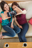 Two friends on the couch taking a selfie with smartphone