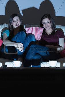 Two smiling friends on the couch watching tv together in the dark