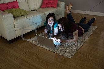 Two happy friends lying on floor using laptop together in the dark