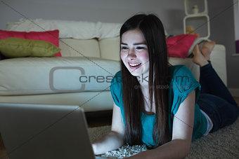 Smiling brunette lying on floor using laptop in the dark