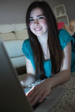 Smiling brunette lying on floor using laptop in the dark looking at camera