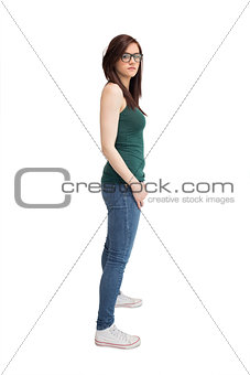 Unsmiling young woman with glasses posing