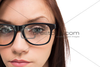 Close up on serious brunette with glasses posing