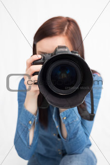 Casual young photographer taking picture of camera